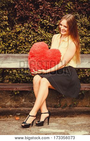 Girl On Bench Holding Heart.