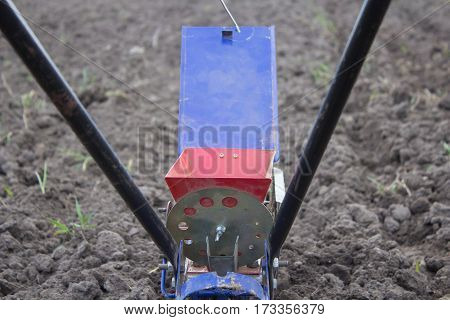 Modern spreader on the with seeds soil