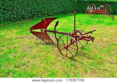 Old Agricultural Machines on a Green Grass