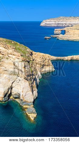 Gozo Malta - The Fungus Rock and the Azure Window at Dwejra bay on a beautiful summer day with clear blue sky sea water