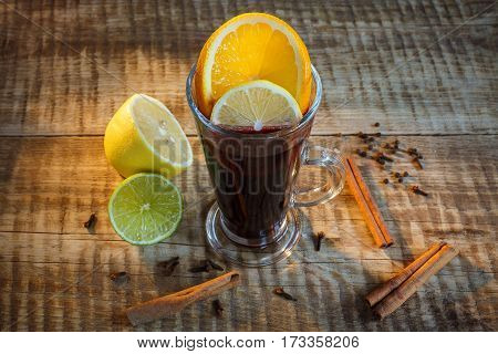 Black tea in glass cup with two slices of lemon and lime, cinnamon and herbs on rustic wood background. Top view. Black tea, milk tea, lemon tea in glass cups on a wooden table, selective focus.