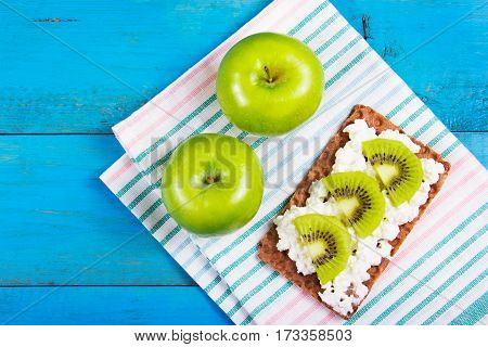 Useful snack quick healthy meal. Grain bread with homemade curd cheese and kiwi slices on a blue wooden background. Two juicy green apples on the table napkins.