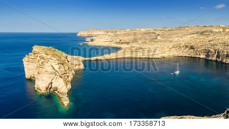 Gozo Malta - Panoramic view of the beautiful Fungus rock with the Azure Window and sail boat at Dwejra bay on a beautiful summer day with clear blue sky