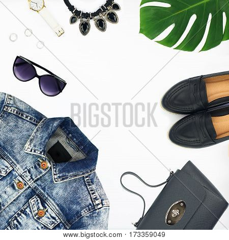 Flat lay of women's fashion set of accessories isolated on white background. Top view of denim jacket leather bag shoes sunglasses and watch