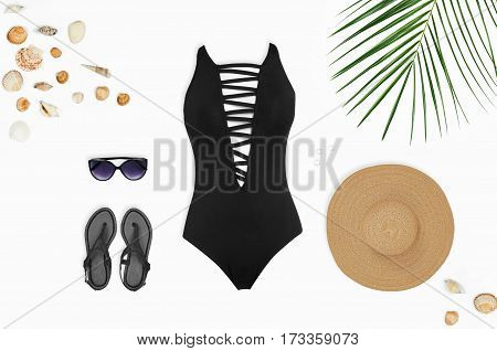 Flat lay beach accessories: swimsuit sunglasses hat sandals with palm branches and shells. Top view on white background.