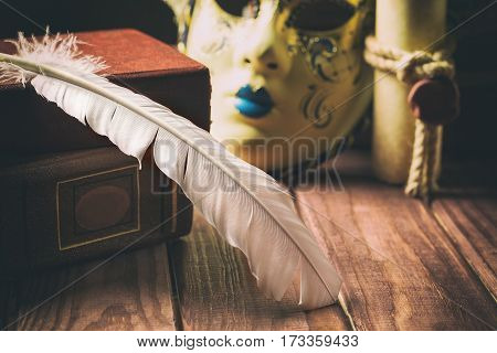 Literature concept. Feather on book near venetian mask and old scroll on wooden background.