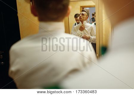 Handsome Groom Preparing For Wedding Ceremony In Hotel Room, Stylish Groomsmen Helping Friend Put On