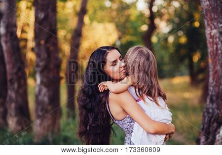 Mother holding a child outdoor. Happy family concept. Baby girl and mom. Mother's Day