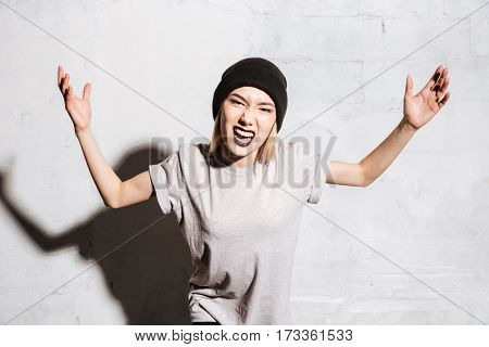 Mad aggressive young woman with black lipstick standing and shouting over white background