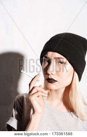 Serious young woman hipster in black hat holding cigarette over white background