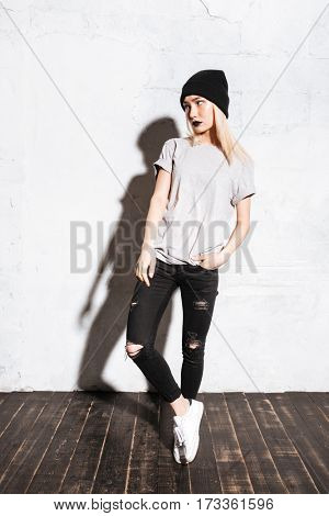 Full length of attractive young woman in hat and torn jeans with black lipstick