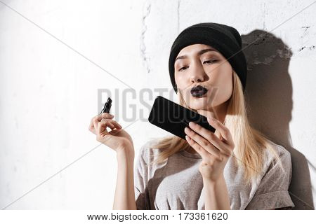 Hipster girl holding pomade and looking at itself in phone over gray background