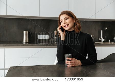Image of young smiling lady dressed in black sweater sitting at kitchen. Talking by mobile phone.