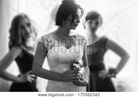 Beautiful Brunette Bride In Stylish White Wedding Dress Posing With Boutonniere Near Gorgeous Brides