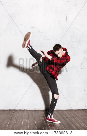 Vertical image of Hipster in shirt doing a high kick in studio. Full length portrait