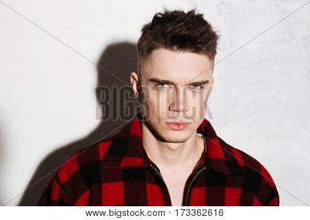 Serious Hipster in shirt looking at camera over gray background