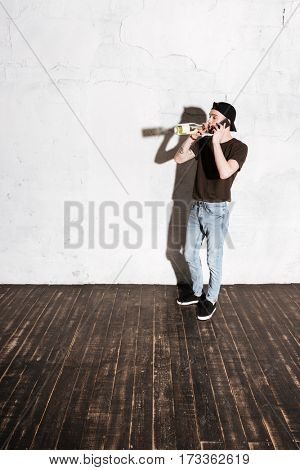 Vertical image of Hipster in snap back drinking wine and talking on phone