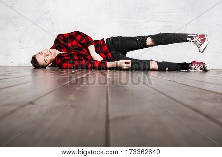 Hipster in shirt lying on the floor and looking at camera