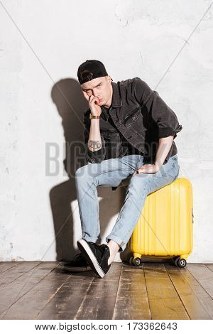 Vertical image of Displeased Hipster in snap back sitting on suitcase and looking at camera