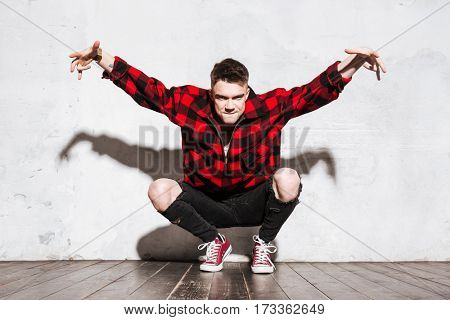 Cool Hipster in shirt sitting and posing in studio and looking at camera
