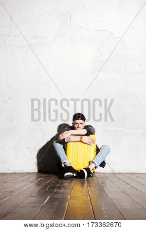 Vertical image of Hipster in snap back sitting on the floor and hugging suitcase