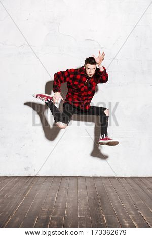 Vertical image of Hipster in shirt jumping in studio. Full length portrait