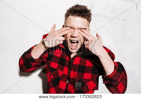 Hipster in shirt holding his fingers on eyes and showing gun gestures over gray background