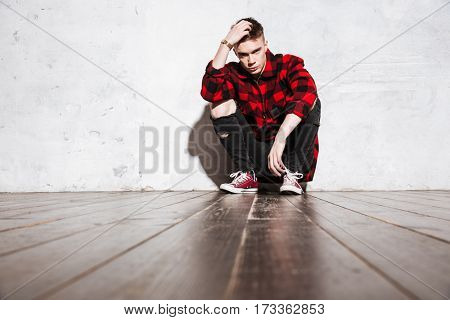 Hipster in shirt posing sitting and looking at camera