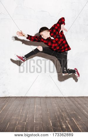 Vertical image of Young Hipster jumping in studio and looking away. Full length portrait