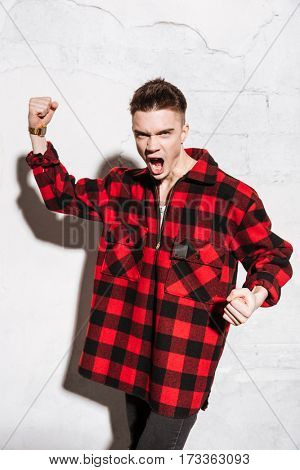 Vertical image of Happy hipster in red shirt which showing victory gestures and looking at camera