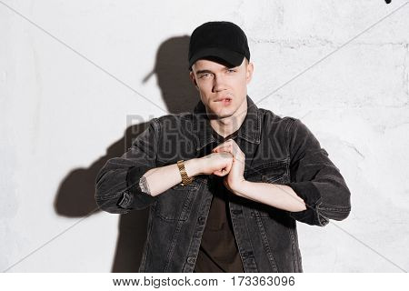 Hipster in snap back crunches fingers and looking at camera over gray background