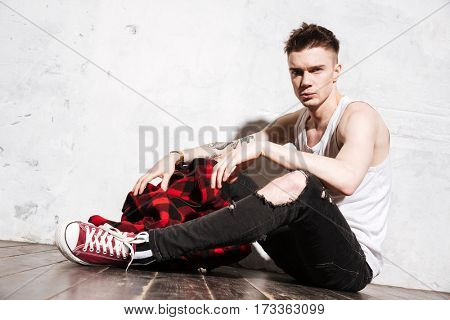 Photo of young serious man sitting on floor posing isolated over wall background. Looking at camera.