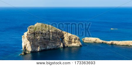 Gozo Malta - The famous Fungus Rock on the island of Gozo on a beautiful hot summer day with crystal clear blue sea water and sky