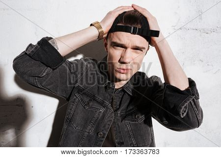 Hipster in snap back holding his head and looking at camera over gray background