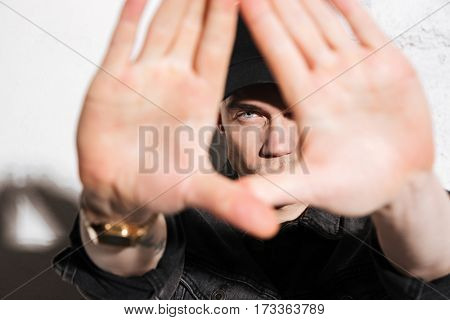 Hipster showing hands at camera and looking through hands over gray background