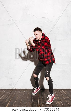Full length portrait of happy hipster in red shirt in studio