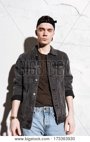 Picture of young attractive man standing on floor wearing watch posing isolated over wall background.