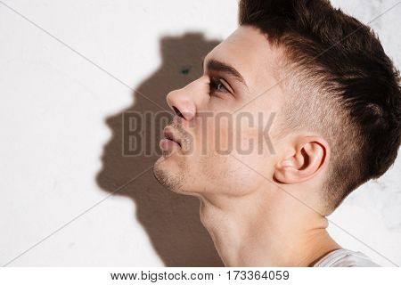Portrait of young handsome man standing on floor posing isolated over wall background. Looking aside.