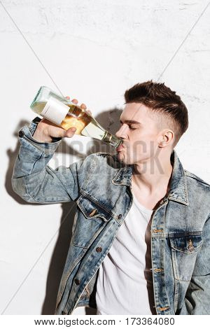 Picture of young handsome man standing on floor drinking alcohol posing isolated over wall background.