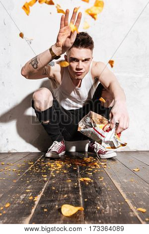 Irritated young man throwing potato chips out from packet over white background