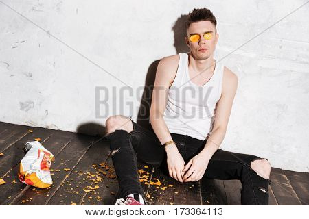Hipster sitting on the floor and having fun over gray background