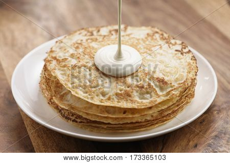 cream pour on freshly made blinis or crepes, simple sweet food, simple sweet food