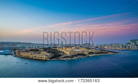Valletta Malta - Panoramic skyline view from the top of Valletta the capital city of malta with Manoel Island and Sliema at sunset