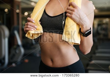 Cropped photo of young beautiful sports lady standing indoors at gym while listening music.