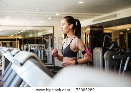 Photo of young amazing fitness woman make sport exercises indoors at gym.