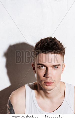 Closeup of confident young man with blue eyes over white background