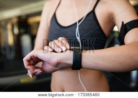 Cropped photo of young sports woman make sport exercises indoors at gym while listening music while looking at watch.