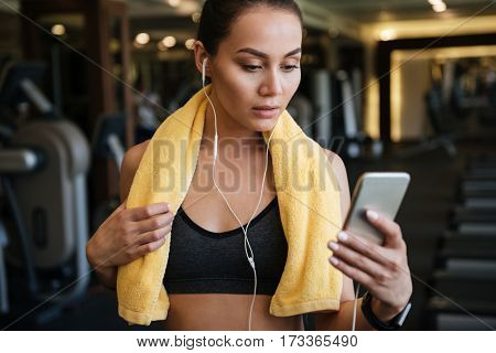 Picture of young beautiful sports lady standing indoors at gym while listening music and chatting by phone.