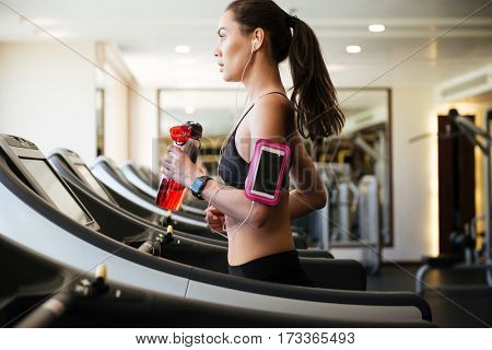 Image of young sports lady make sport exercises indoors at gym while listening music. Holding water.