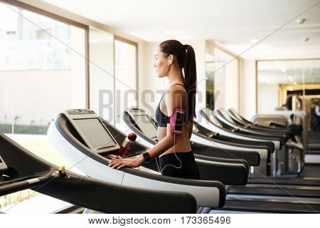 Photo of young pretty fitness woman make sport exercises indoors at gym.